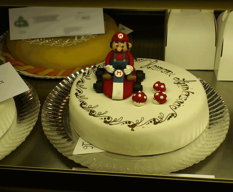 Un gâteau décoré avec Super Mario Kart et quelques champignons rouges