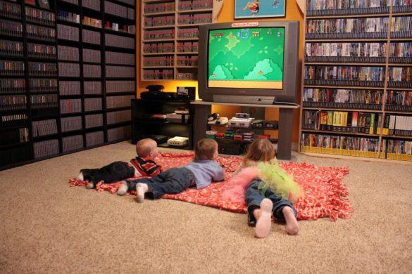 enfants couchés devant une television avec le jeu super mario world
